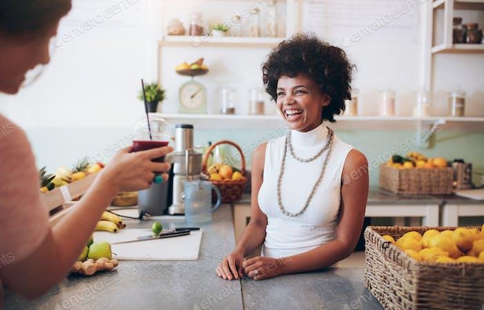Lächelnde junge Frau im Gespräch mit einem Kunden in Saftbar