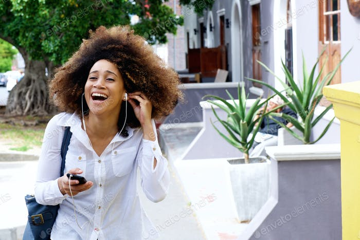 Smiling young woman walking with earphones ad mobile phone
