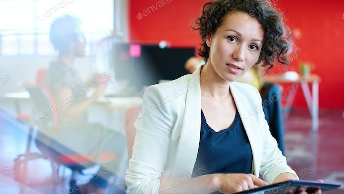 Selbstbewusste Designerin arbeitet auf einem digitalen Tablet in rot kreativen Büroflächen
