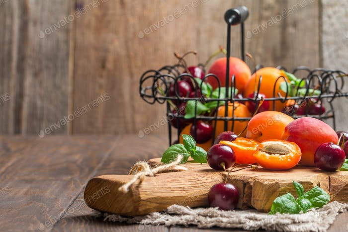 Apricots and cherries on rustic background