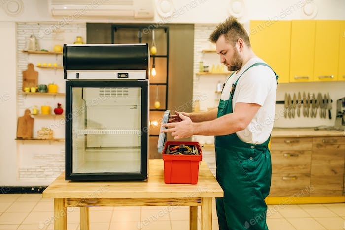 Worker with toolbox repair refrigerator at home