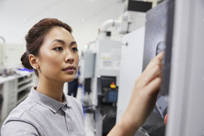 Female Engineer Operating CNC Machinery In Factory