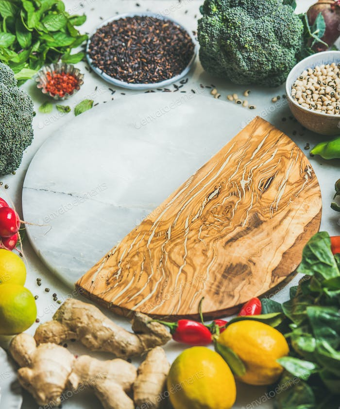 Vegetables, beans, grains, greens, fruit, spices, round board in center