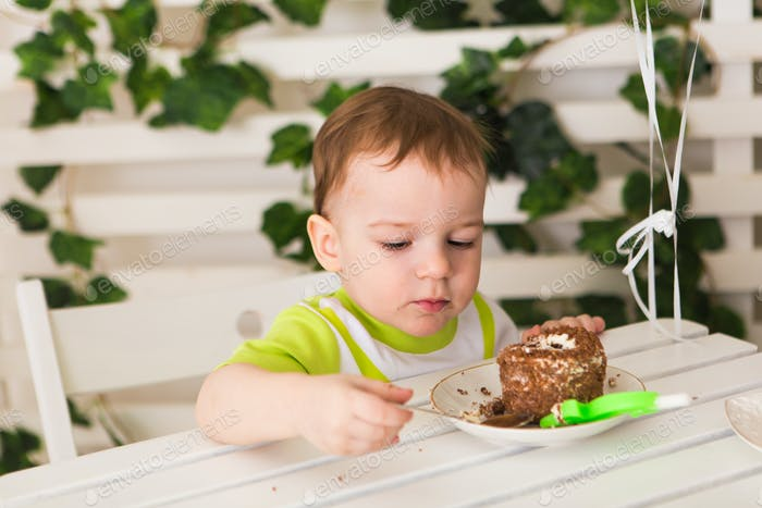 kid boy celebrating his birthday holds piece of cake