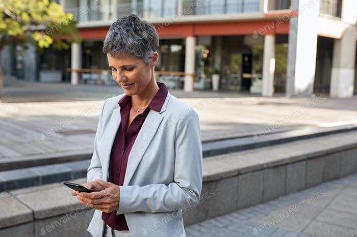 Mature businesswoman using phone on street