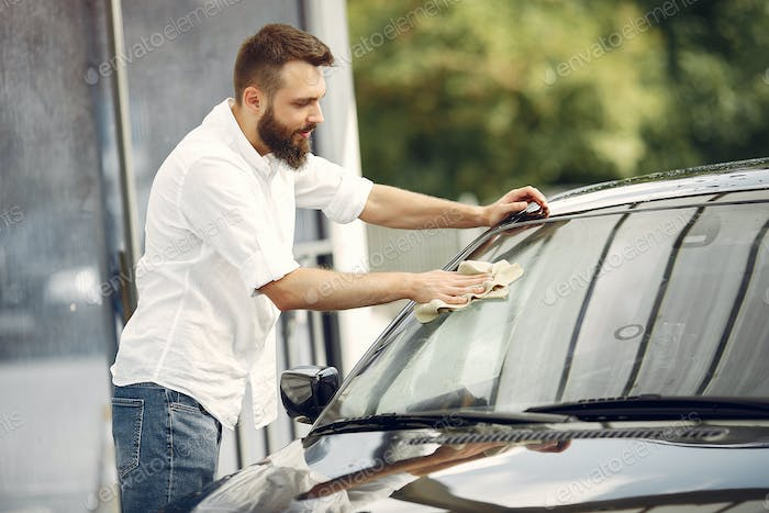 Man in a white shirt wipes a car in a car wash