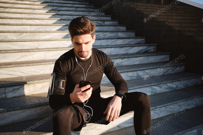 Young attractive sporty man thoughtfully using cellphone on stairs after workout outdoor