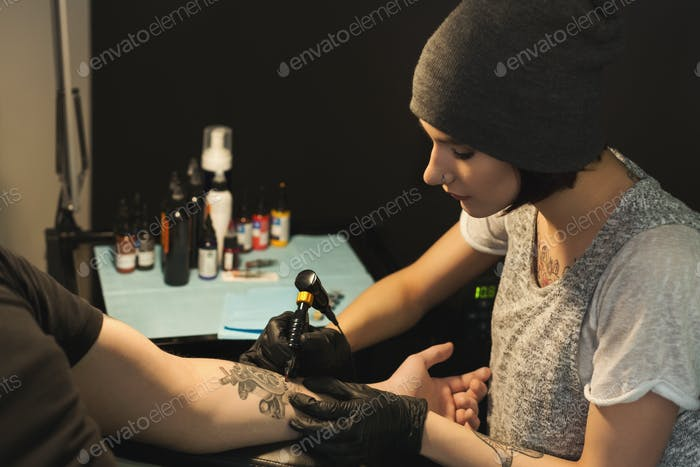 Thumbnail for Young woman tattooist doing tattoo on male arm