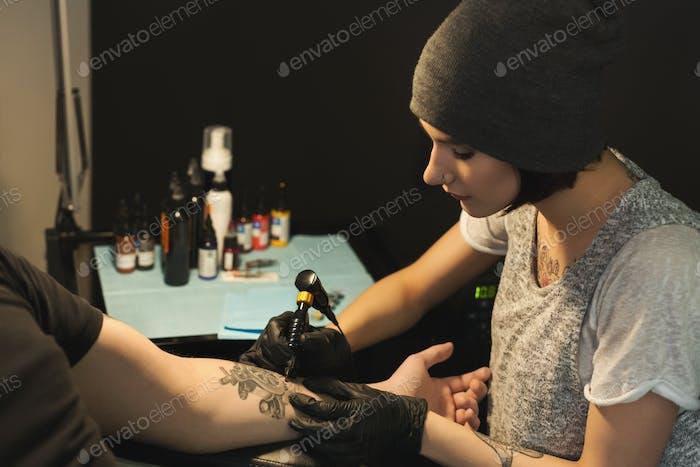 Junge Frau Tätowiererin tun Tattoo auf männlichen Arm