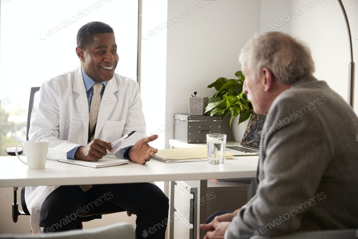 Senior Man Having Consultation With Male Doctor In Hospital Office