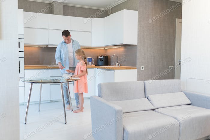 Dad and daughter preparing a cake at home