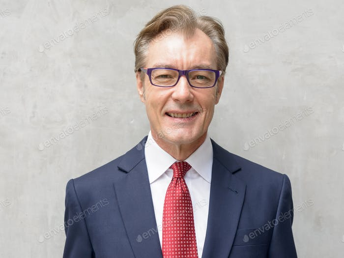 Face of happy handsome mature businessman with eyeglasses smiling against concrete wall