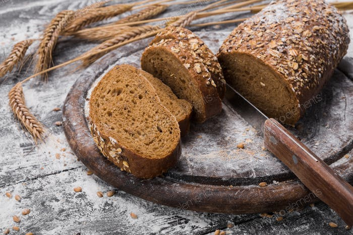 Bakery concept background. Whole grain rye sliced bread and knife