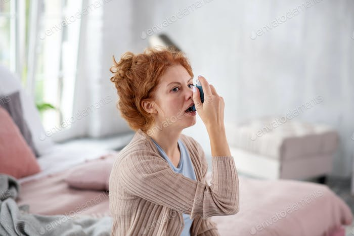 Red-haired pretty woman having unexpected asthma attack