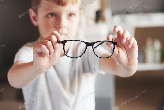 Kleiner Junge hält seine neue Brille in der Arztpraxis