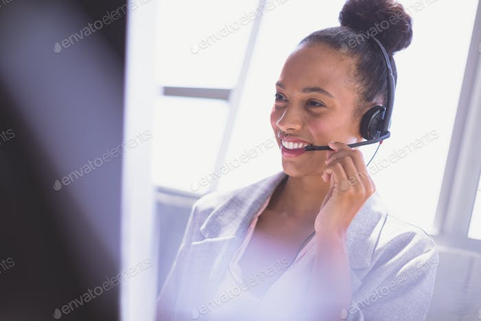 Businesswoman talking on headset while working on computer at desk in the office