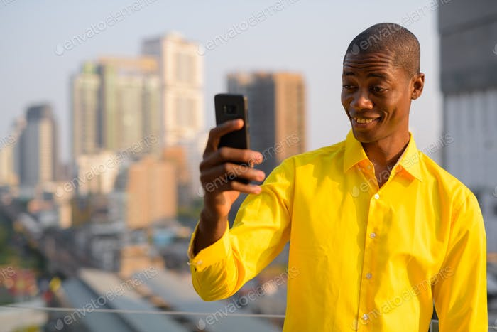Happy young bald African businessman taking selfie against view of the city