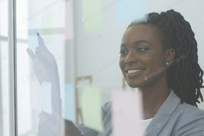 Afro Lady Putting Sticky Notes On Glass Board At Workplace