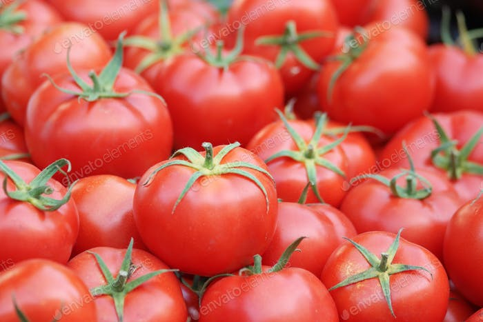 Pile of red ripe tomatoes at grocery store.
