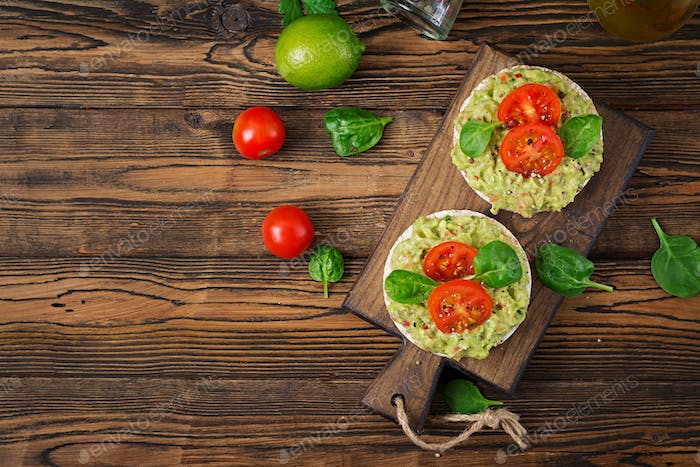 Healthy breakfast. Sandwich crisp bread with guacamole and tomatoes