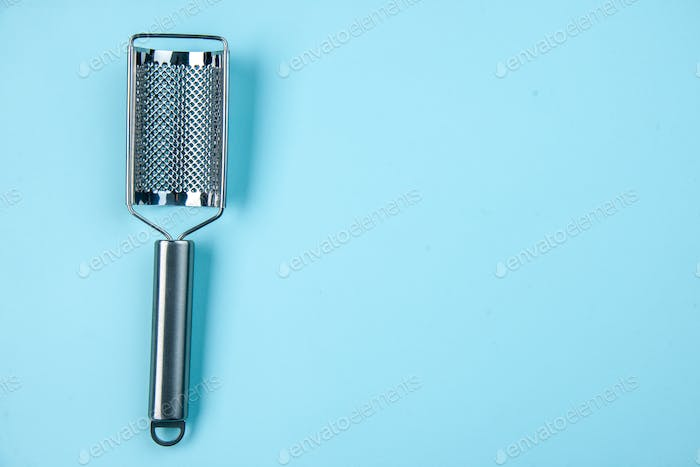 Top view of stainless kitchen tool lying on the right side on pastel blue background with free