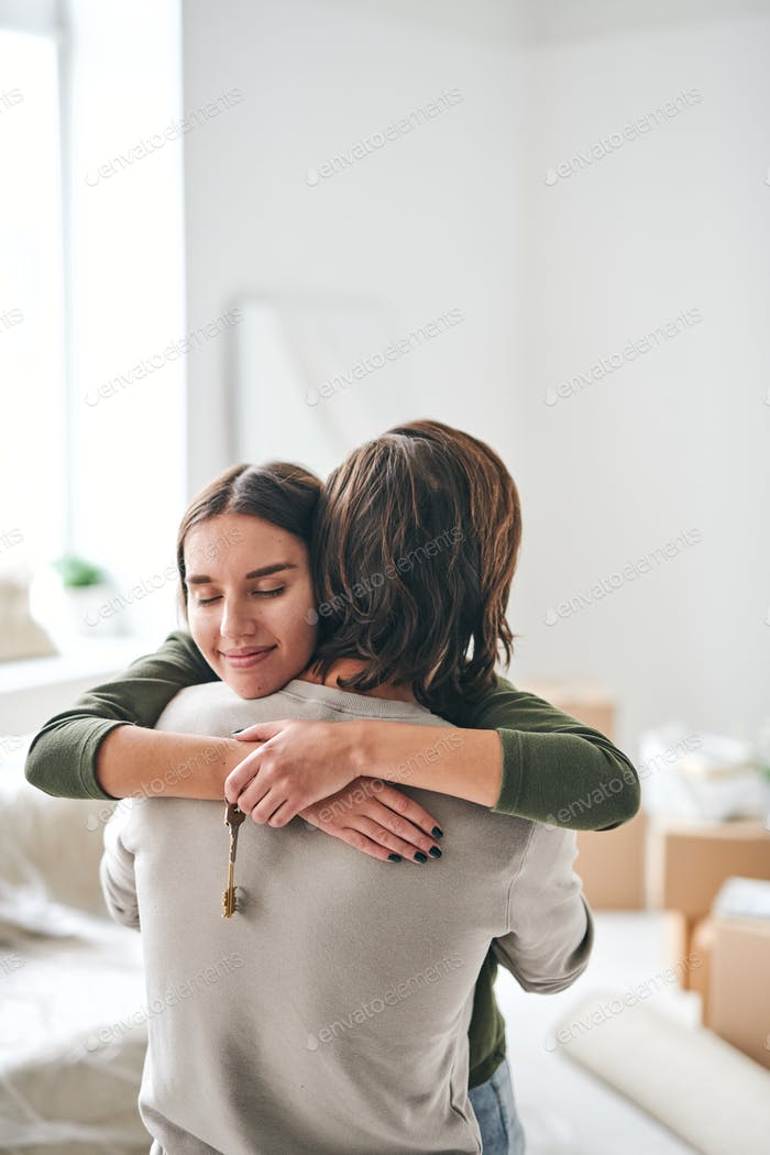 Happy young wife with key from new flat giving hug to her husband