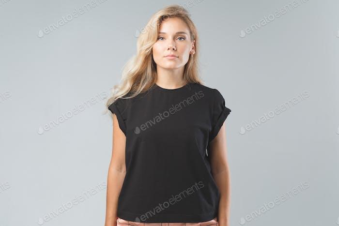 Blonde schöne Frau in schwarzem T-Shirt. Studio-Shooting