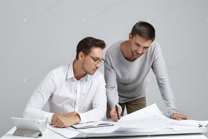 Teamwork, Job- und Kooperationskonzept. Bild von zwei begeisterten talentierten jungen bärtigen Ingenieuren