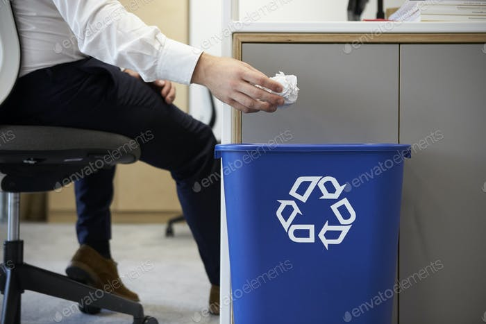 Man dropping screwed up paper into recycling bin, close up