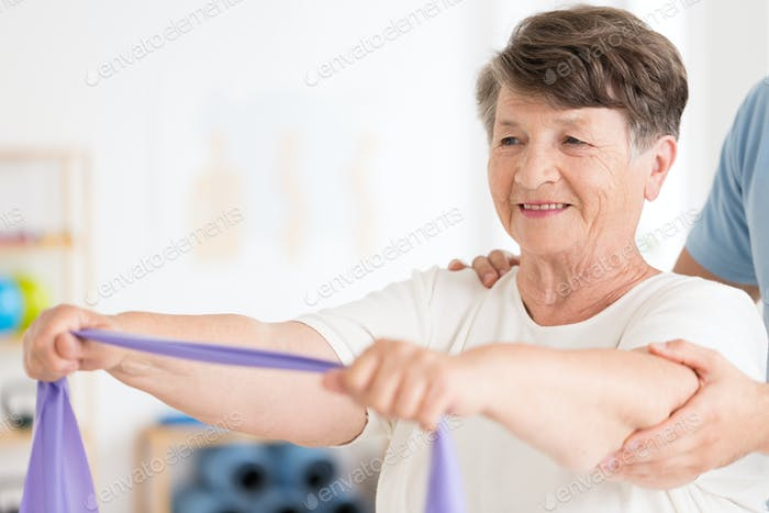 Elderly woman pulling elastic band