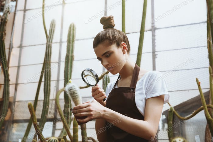 Serious young woman standing in greenhouse near plants