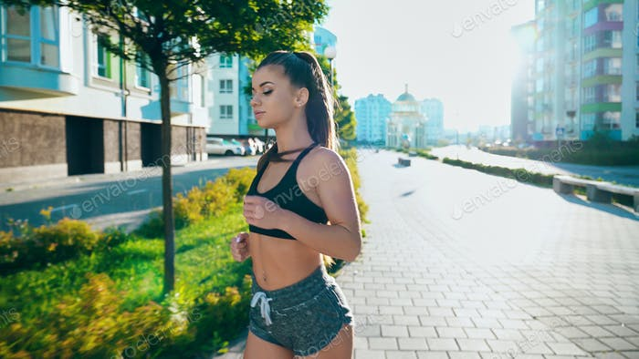 Active woman running in morning city streets