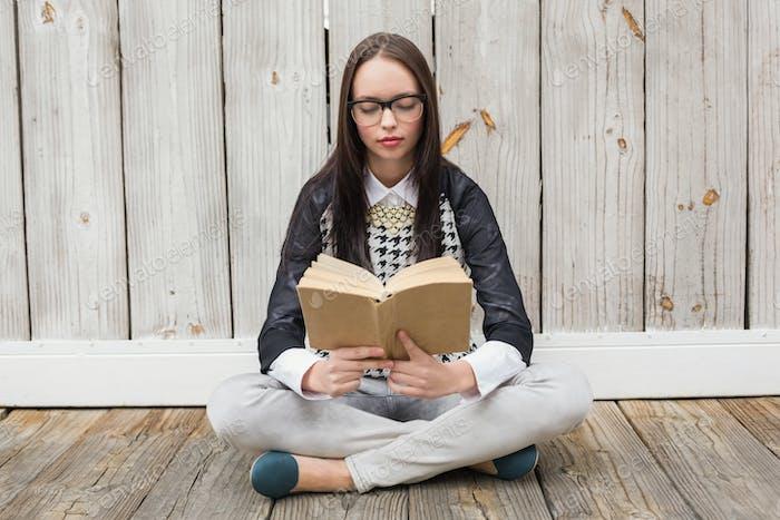 Ziemlich hipster liest ein Buch gegen gebleichte Holzbretter