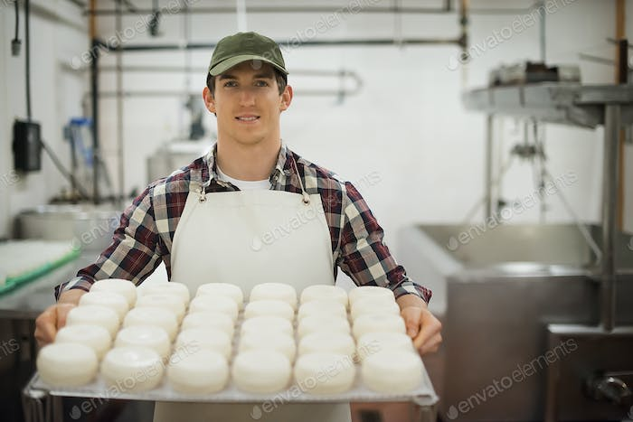 Dairy building with large wheels of cheese maturing, man holding trays of produce.