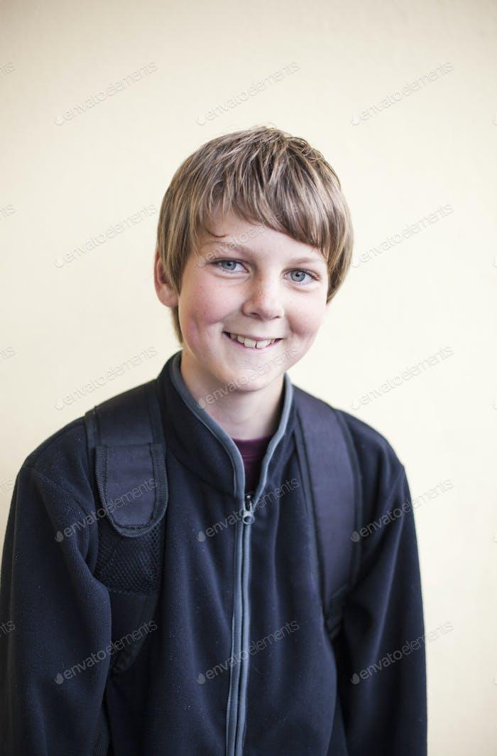 Porträt von glücklich junior high schoolboy stehend gegen Wand