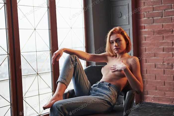 Natural breast. Girl sits on the chair. Half naked attractive young woman showing her hot body