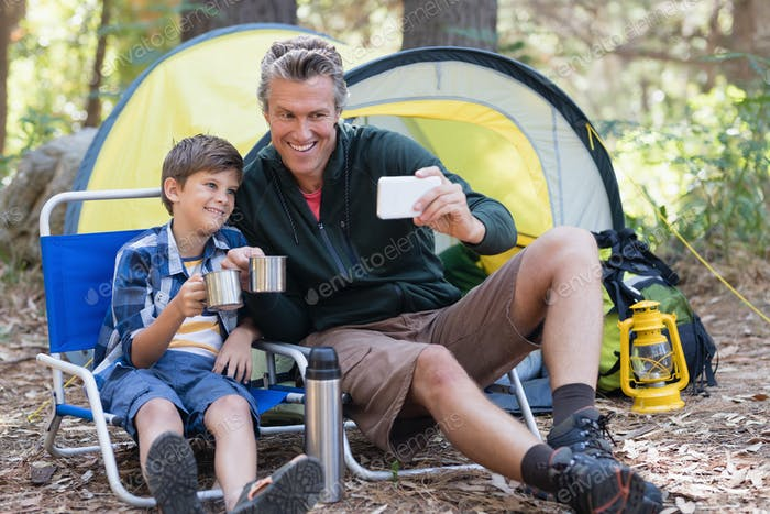 Happy father and son taking selfie while having hot drink in forest