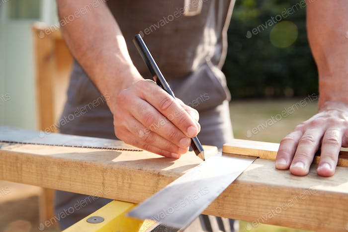 Close Up Male Carpenter Measuring Wood Using Set Square Outdoors