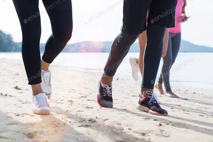 Closeup Of Group Of People Running On Beach Feet Shot Sport Runners Jogging Working Out Team Men And