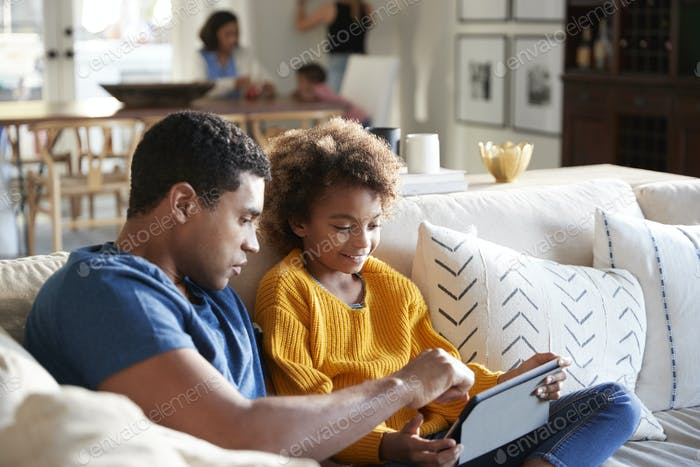 Pre-teen girl sitting on sofa in the living room using tablet computer with her father