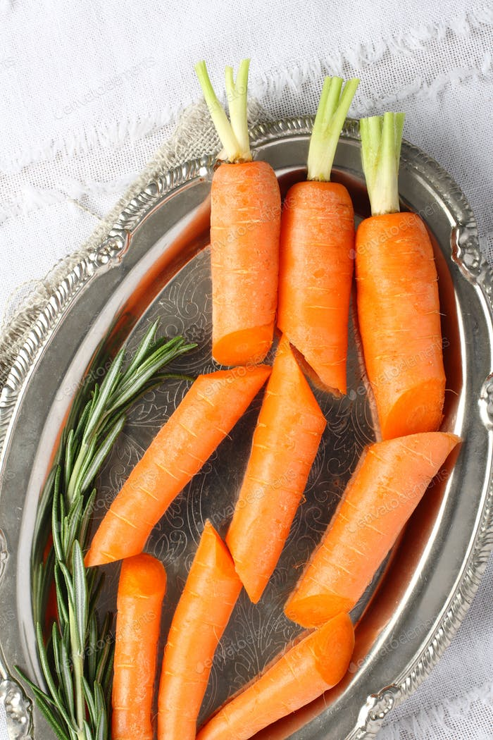 Fresh organic raw sliced carrots with rosemary on metal plate