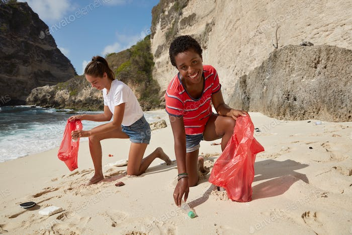 Waste disposal concept. Female volunteers clean beach from garbage, plastic, hold trash bags, collec
