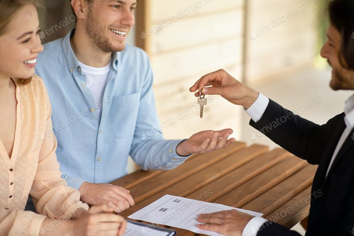 Realtor handing over keys of new house to happy married couple at table outdoors
