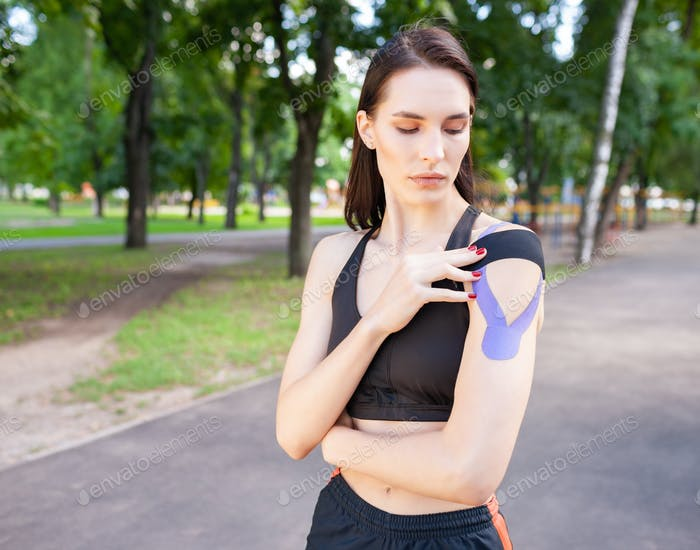 Muscular woman putting kinesiological taping on shoulder outdoors