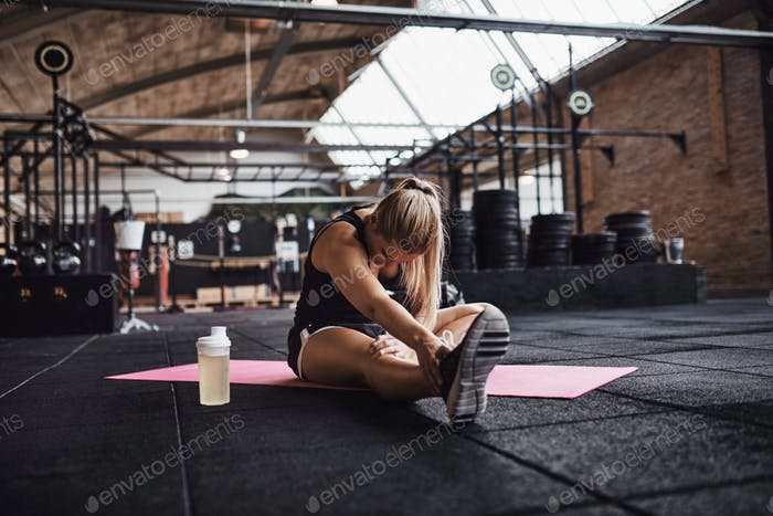 Fit young woman stretching at the gym before working out