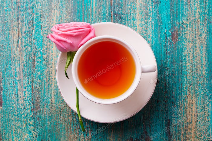 Cup of Tea with Pink Rose. Top View. Copy Space. Colorful Turquoise Wooden Background.