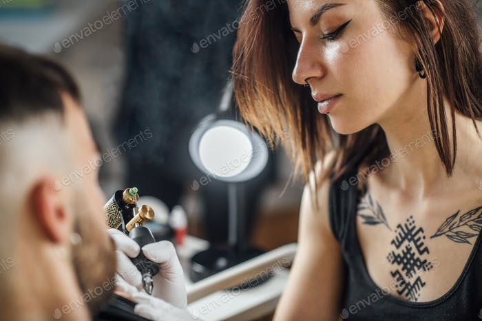 Professional Female Tattooist Working in a Tattoo Studio
