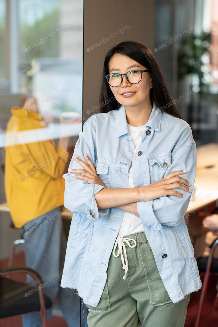 Happy young Asian businesswoman crossing her arms by chest against colleague
