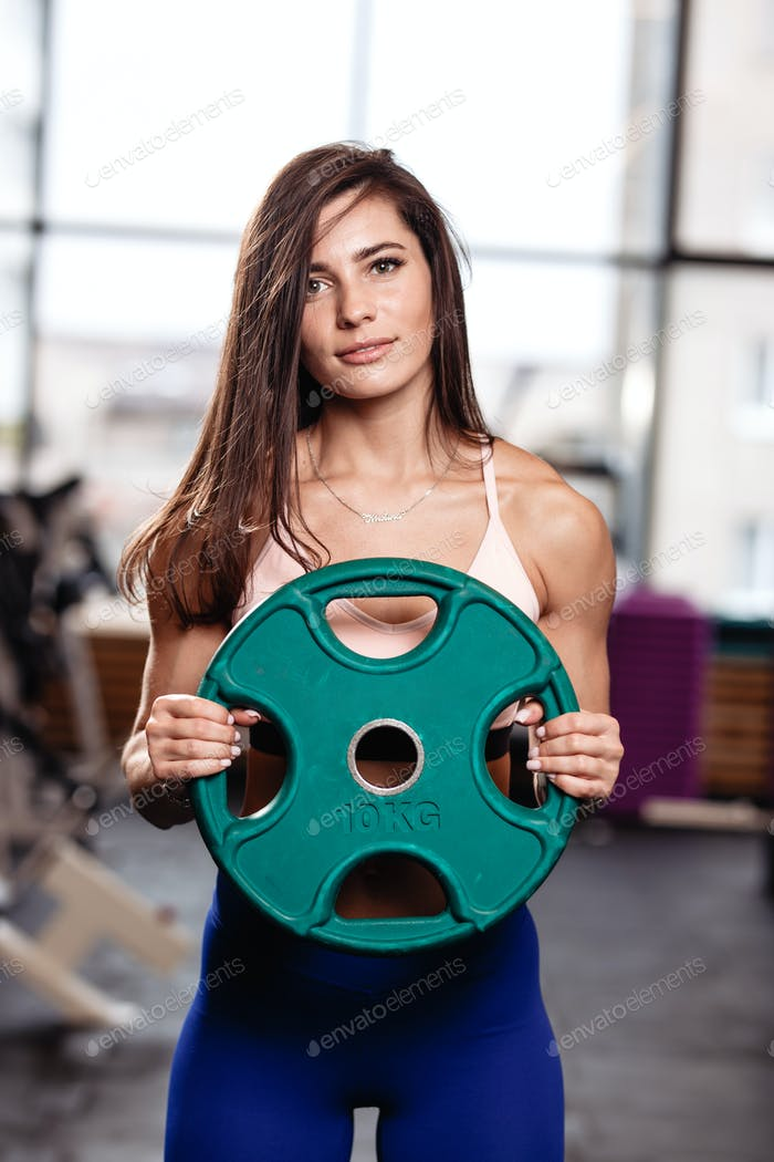 Athletic young brunette girl holds a heavy plate in her hands in the modern gym