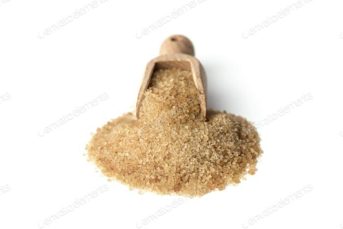 Brown cane sugar crystals in wooden scoop
